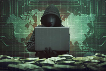 Hooded man with anonymous mask using laptop to hacking bank