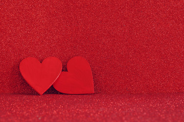 Wooden red hearts on red shiny background
