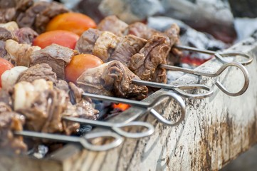 Grilled shish kebab on metal skewer closeup. Smoking beef meat and cherry tomatoes on a skewer in a steel brazier.