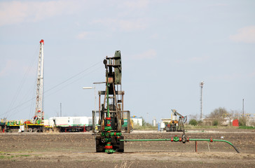 Pump jack and oil drilling rig on oilfield