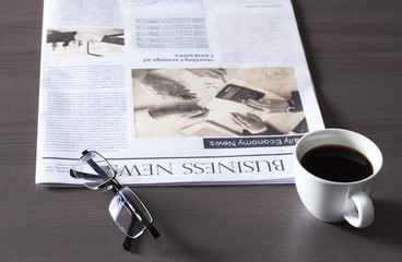 Newspaper with eyeglasses on wooden table