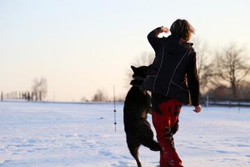Frau spielt mit Hund im Schnee