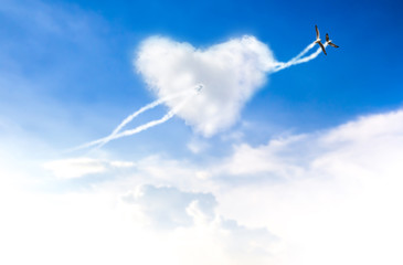 Love is in the two bird flying blue sky with hearts shape clouds