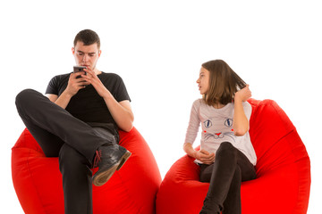 Young man and girl sitting on red beanbag chairs