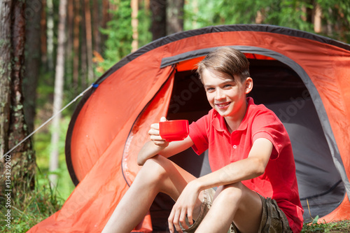 Happy teen boy sitting at a c&ing tent in a summer forest holding a cup of  sc 1 st  Fotolia.com & Happy teen boy sitting at a camping tent in a summer forest ...