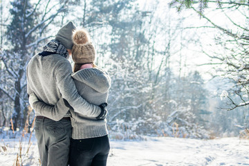 Couple hugs in winter forest