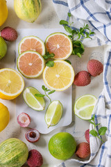 Variety of whole and sliced citrus fruits pink tiger lemon, lemon, lime, mint and exotic lichee on white chopping board with kitchen towel over white concrete textured background. Top view. Healthy