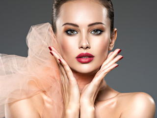 closeup face of a fashion woman with stylish makeup, red nails a