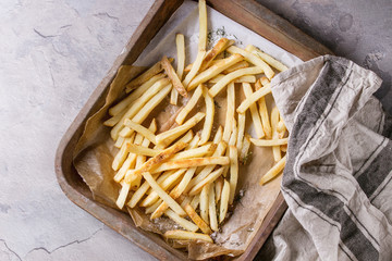 Fast food french fries potatoes with skin served with salt on baking paper in old rusty oven tray with kitchen towel over gray texture background. Top view, space for text