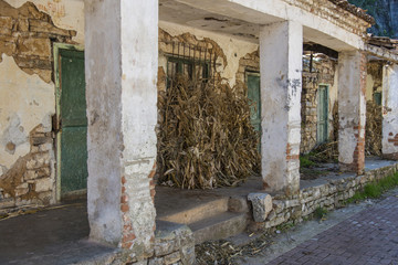 Dried corn stalks straw in backyard of typical Albanian old house