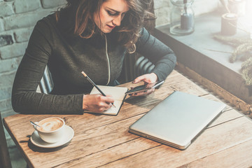 Young business woman sitting at wooden table in cafe and use smartphone while making notes in notebook. Nearby is cup of coffee and closed notebook. Student learning online. Girl using gadget.