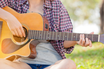 Young asian girl in forest with guitar in the garden