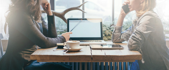 Teamwork, two young businesswomen sitting across table from each other. On table laptop, coffee cup and tablet computer. First girl showing pencil on computer screen, other is talking on cell phone.