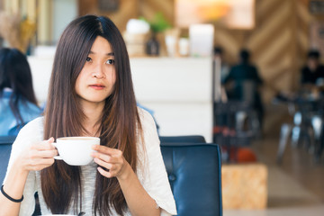 Asian women sitting in library with cup of coffee to make a idea