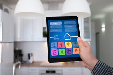 male hand holding tablet app smart home kitchen in house
