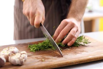 Ostrożne siekanie warzyw. Dłonie kucharza siekającego zioła na desce kuchennej