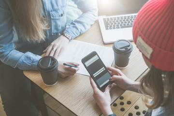 Top view, close-up smartphone in female hands. Meeting of two friends in cafe.Girls learn online, drinking coffee. First woman takes notes,and second uses a smartphone.Freelancers work outside office.