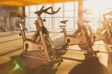 Modern gym interior with equipment, fitness exercise bikes