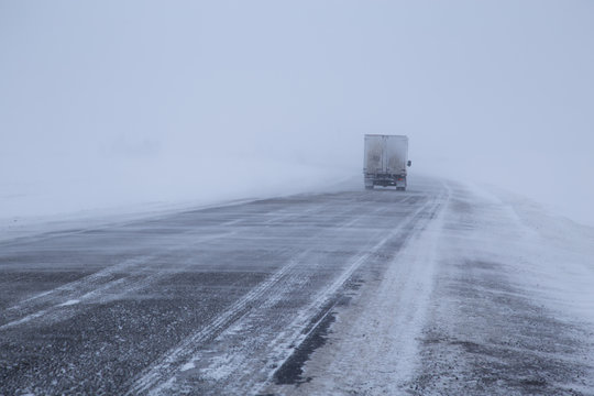 Car on winter road in a snowstorm and bad visibility