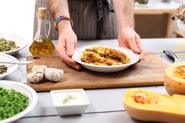 Potrawa kuchni wegańskiej. Kucharz przygotowuje danie obiadowe
