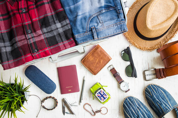 Travel preparations, men's casual outfits with accessories on white rustic wooden background