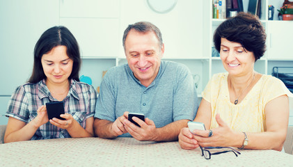 Smiling mature parents with daughter sitting with phones