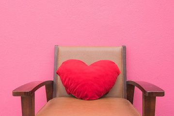 red heart pillow on the chair wall pink background .