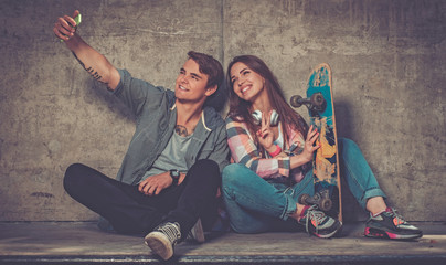 Cheerful couple with with skateboard outdoors