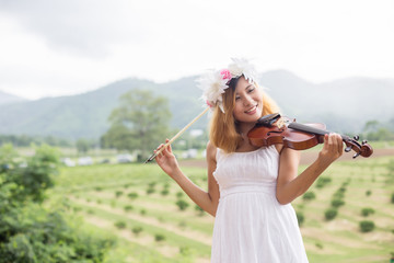 Young hipster musician woman playing violin in the nature outdoo