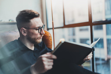 Attractive stylish businessman reading black book while sitting in vintage chair at his modern office.Young man relaxing after work day.Panoramic windows on blurred background.Horizontal,film effect.