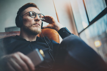 Portrait handsome bearded man wearing glasses,headphones listening to music at modern home.Guy sitting in vintage chair,holding smartphone and relaxing.Panoramic windows background.Blurred.