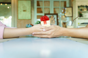 A couple hands holding a golden gift box with red ribbon in rest