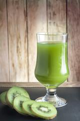 Kiwi Juice and kiwi fruit arranged on a wooden table.