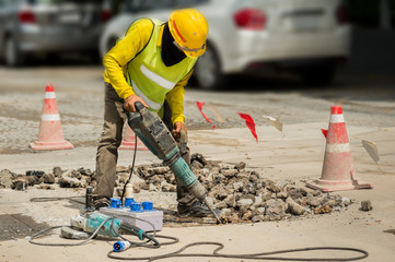 Worker drilling concrete driveway with jackhammer.
