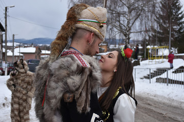 Young Bulgarian couple in folk costumes kissing on the street during Surva festival