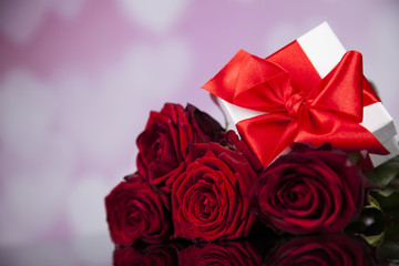 Red roses and gift box, love background