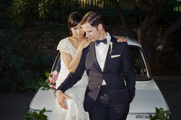 Man and woman sitting on car bonnet wearing dress and suit