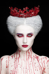 Mysterious beauty portrait of snow queen covered with blood. Bright luxury makeup. White demon eyes.