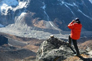 Mountain Climber in warm Jacket taking Picture of Valley