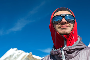 Cheerful young Mountain Climber in Sunglasses and protective Clothing