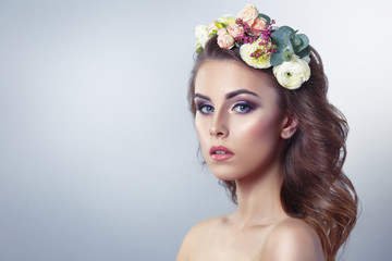 Delicate spring beauty portrait of a beautiful girl with a wreath of flowers on his head isolated on a gray background.