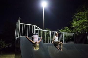 Siblings playing on slide at night
