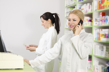Beautiful female pharmacist talking to the phone with client