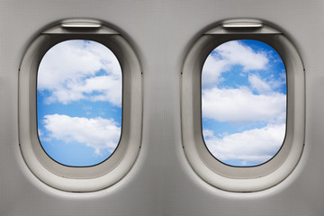 Sky with white clouds viewed from inside an airplane windows