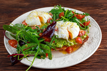 Smashed avocado and poached egg toast on green salad for breakfast