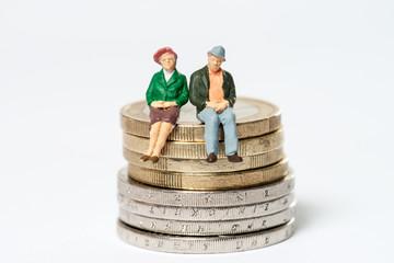 Rentner / älteres Ehepaar sitzt auf Euromünzen