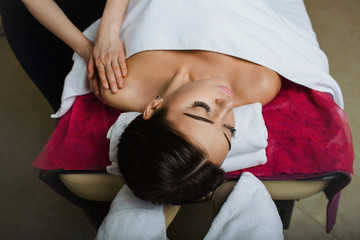 Attractive brunette woman getting massage lying on a massage table, hands working on massaging woman's shoulder. Relaxing spa treatment at spa salon, top view.