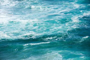 Blue Fresh Water Whitecap Waves Wash Ashore onto a Sandy Beach.