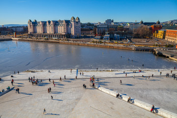 Bjorvika bay and embankment. People are walking around Opera house.