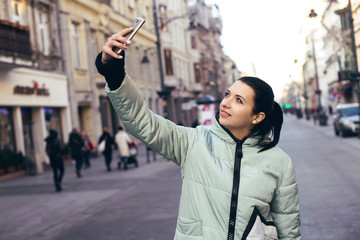 Young pretty woman taking selfie outdoors